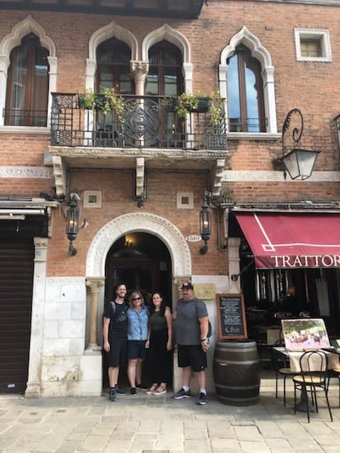 The Lombardo family posing next to the restaurant from their painting.