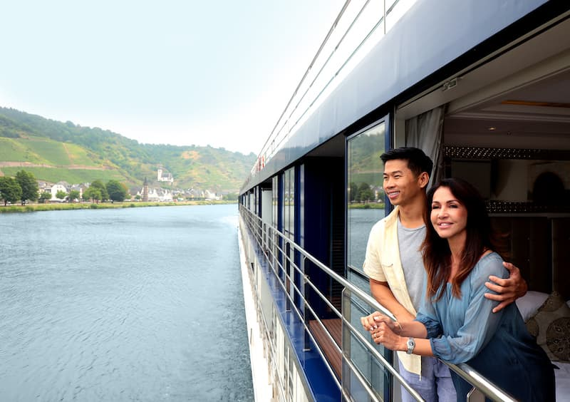 Two people standing on the balcony of their river cruise ship cabin