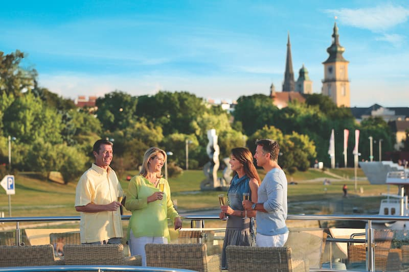 Two couples having champagne on the top deck of their European river cruise ship