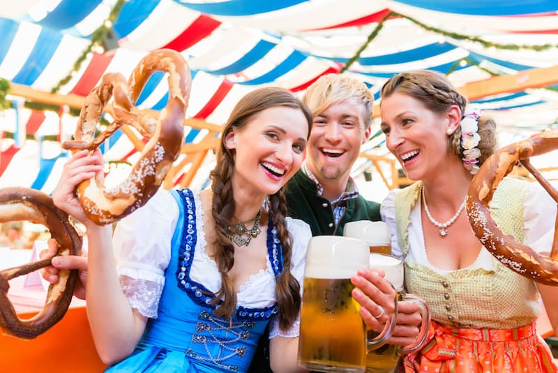 Three people laughing and holding their beer and pretzels during Oktoberfest in Munich