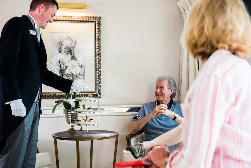 Uniworld river cruises butler serving afternoon tea to a guest on the ship