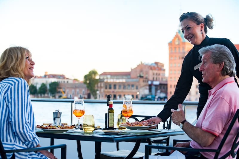 Two people having their dinner on the deck of a Uniworld river cruise ship